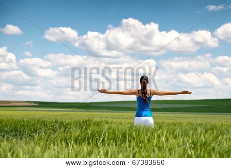 Image of a girl in a wheat field standing in the distance with her back to the camera and her arms outspread in celebration of a beautiful sunny summer day and freedom