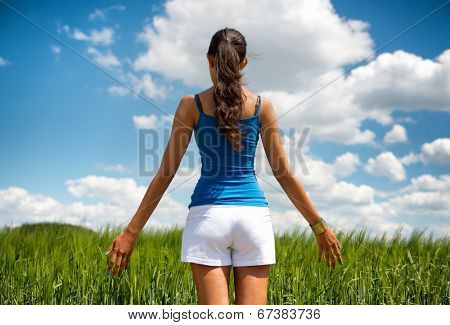 Shapely young woman in shorts enjoying a day in nature standing with her back to the camera looking out over a green field under a sunny blue cloudy summer sky