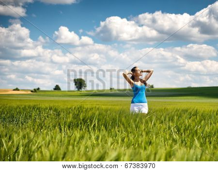 Beautiful girl relaxing in a green wheat field standing with her arms raised above her head and a lovely serene smile against a pretty blue summer sky with fluffy white cloud