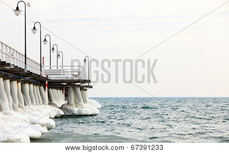 Winter Scenery. Frozen Baltic Sea. Ice Formations Icicles On Pier Poles