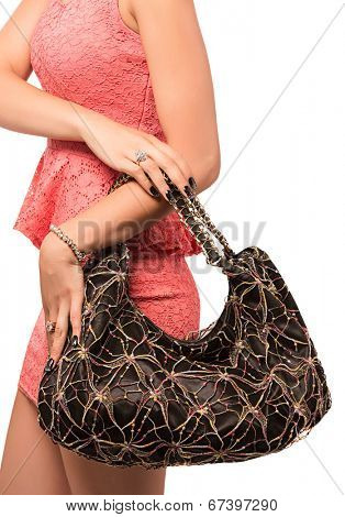 Closeup of woman with embroidered lace black evening bag. Wearing mini lace dress. Isolated on the white studio background.