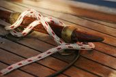 foto of dock  - White rope coiled on a wooden dock and tied to a metal dock cleat - JPG