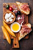 stock photo of melon  - Prosciutto ham Slices of melon cantaloupe Mozzarella cheese and Olives on cutting board - JPG