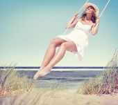 image of swing  - Beautiful Cheerful Woman Swinging by the Beach - JPG