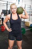 pic of slam  - Attractive and blonde young girl with a slam ball on the shoulder after workout at a fitness gym center - JPG