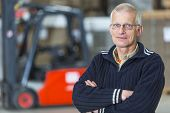 image of forklift  - A forklift driver is posing in front of his forklift - JPG