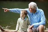 pic of grandfather  - Grandfather and grandson sitting by lake - JPG