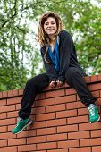 foto of dread head  - Original funny girl with dreads sitting on the wall - JPG