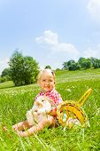 stock photo of cuddle  - Happy small girl cuddling rabbit in green field with basket with Eastern eggs nearby - JPG
