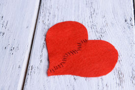 image of heartbreaking  - Broken heart and thread on wooden background - JPG