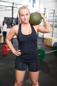 stock photo of slam  - Attractive and blonde young girl with a slam ball on the shoulder after workout at a fitness gym center - JPG