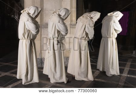 Four monks walking in a row along a pillar of a medieval church (composite image with only 1 man)
