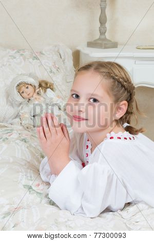 Innocent little girl praying in her bedroom