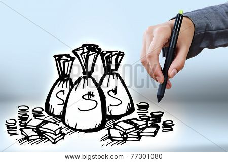 Close up of businessman hand drawing money bags