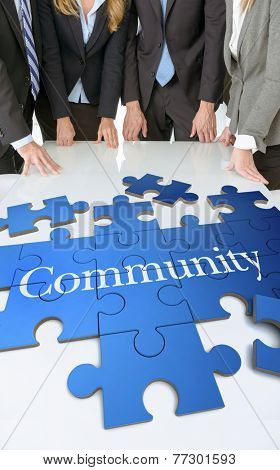 Meeting with people around a table with a puzzle with the word community