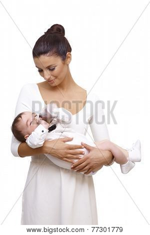 Beautiful young mother holding baby boy in arm. Baby drinking from feeding bottle, wearing bow tie and shirt.