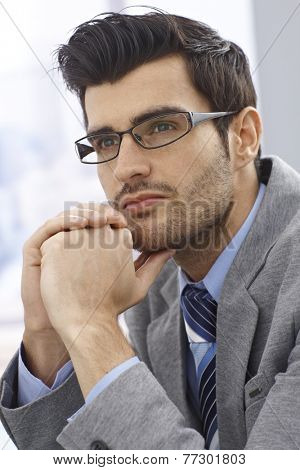 Portrait of handsome young daydreaming businessman looking away.