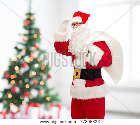 christmas, holidays and people concept - man in costume of santa claus with bag looking far away over living room and tree background