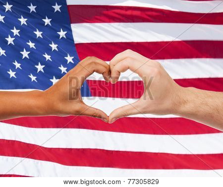 love, patriotism, gesture, peace and people concept - closeup of two hands showing heart shape over american flag