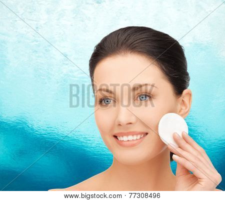 beauty, people and health concept - beautiful smiling woman cleaning face skin with cotton pad over ripple blue water background