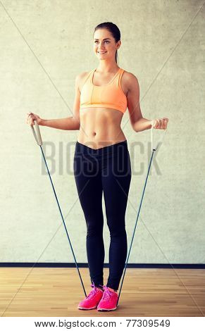 fitness, sport, training and lifestyle concept - smiling woman doing exercises with expander in gym