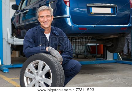 Portrait Of Happy Mature Mechanic At Repair Service Station Holding A Tyre