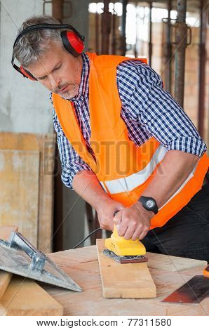 Portrait Of Male Carpenter Wearing Earmuff Smoothing Wood With Polisher At Construction Site