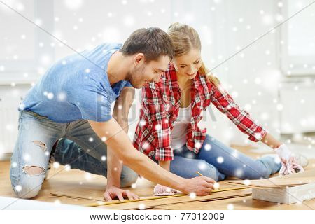 repair, building, family, people and home concept - smiling couple measuring parquet plank on floor