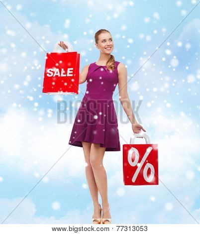 sale, gifts, christmas, holidays and people concept - smiling woman in purple dress holding shopping bags with percentage sign over blue sky and clouds background
