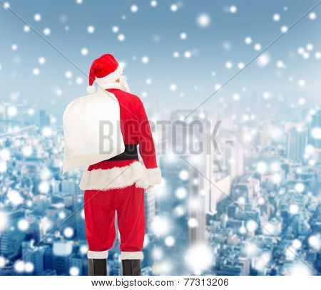 christmas, holidays and people concept - man in costume of santa claus with bag from back over snowy city background