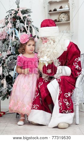 Girl in a pink dress talks to Saint Nicolas