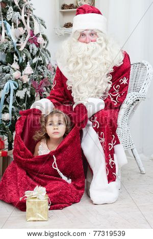 Little girl sits in Saint Nicolas bag