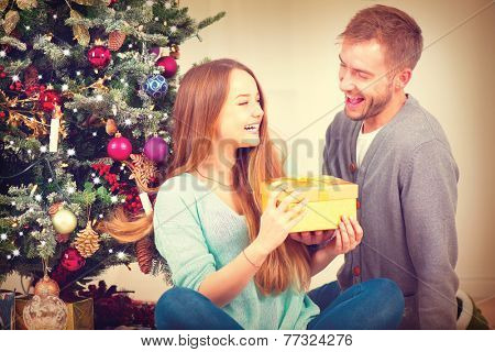 Christmas Gift. Happy Couple with Christmas and New Year Gift at Home. Smiling Family Together. Christmas tree