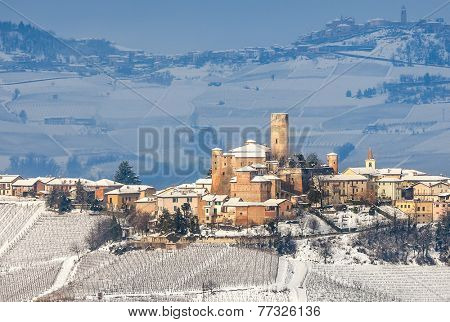 Small town of Castiglione Falletto and vineyards on hills covered with snow in Piedmont, Northern Italy.