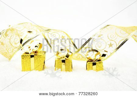 Golden Christmas Gifts With Golden Ribbon On Snow