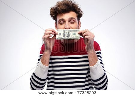 Happy man kissing dollar bill over gray background