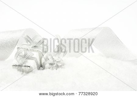 Three Silver Christmas Gifts With Silver Ribbon On Snow