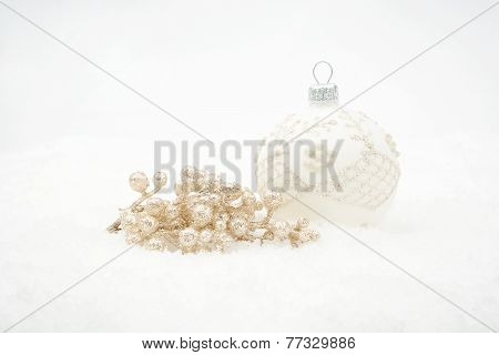 White Christmas Bauble With Gold Decoration On Snow