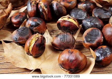 some roasted chestnuts and autumn leaves on a rustic wooden table