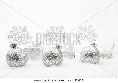 Silver Christmas Gifts And Baubles With Snowflakes On Snow