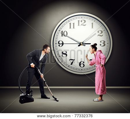 quarrelsome wife screaming at smiley husband with vacuum cleaner. photo in dark room with big clock on the wall