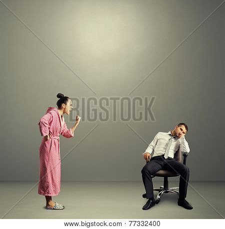 angry wife screaming at lazy husband in the grey room