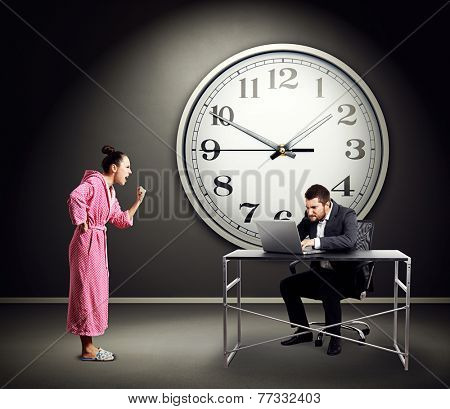 emotional woman screaming at busy businessman over dark wall with big clock