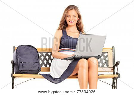 Young female student working on a laptop seated on a bench isolated on white background