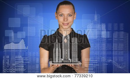 Beautiful businesswoman holding tablet pc with layouts on it. Buildings, figures. letters and diagra