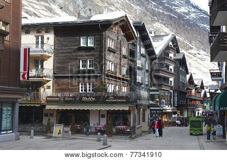 Unidentified tourists explore traditional wooden houses street in Zermatt, Switzerland.