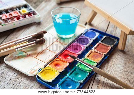 Set Of Watercolor Paints, Art Brushes, Glass Of Water And Easel With Painting On Old Table.