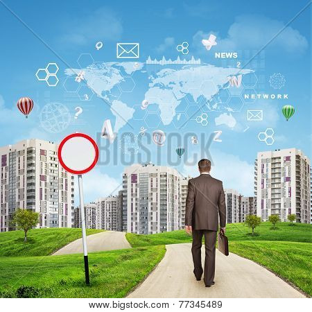 Businessman walking along road through green hills towards city. Charts and other virtual items in s