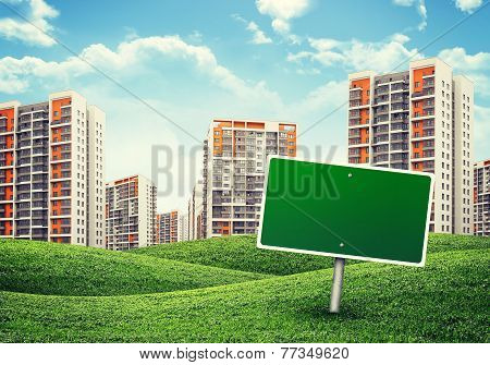 high-rise buildings over green hills and billboard