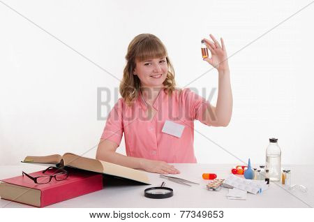 Pharmacist Sitting At A Table With An Ampoule